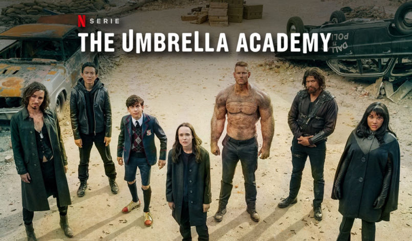 """Die 7 Hauptcharakter der Serie """"The Umbrella Academy"""" stehen auf einem Schrottplatz und schauen alle in die Kamera"""