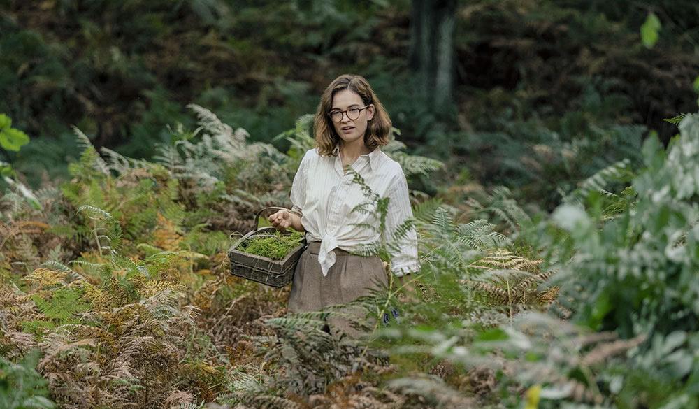 Lily James als Peggy Piggott im Wald.