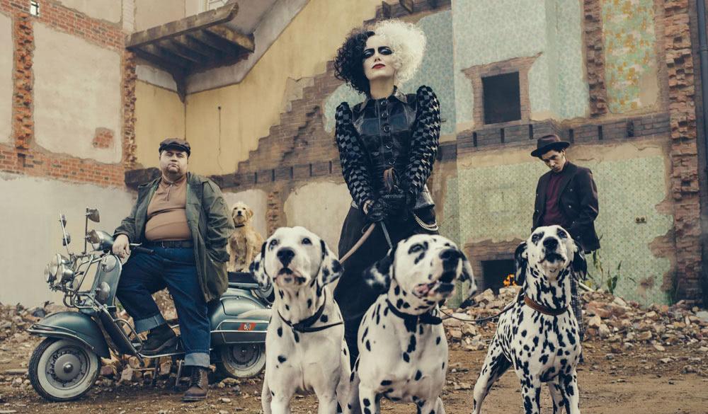 Das Bild zeigt Emma Stone als Cruella zusammen mit ihren Handlangern Horace und Jasper sowie dreier Dalmatiner.