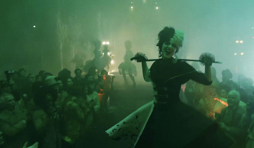 Das Bild zeigt Emma Stone als Cruella in voller Dalamtiner-Montur, die bei einer ausgefallenen Modenshau mit ROckmusik das Establishment aufmischt.
